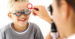 Young Medical Professional Checking the Eyes of Young Boy (8-10)